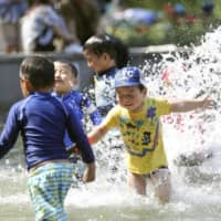 Children play in the water at a park in the city of Osaka on Saturday as temperatures exceeded 30 C in the city and in several other parts of the country. | KYODO