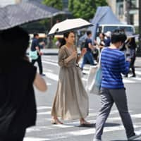 People cross a street in Tokyo's Ginza district on Monday amid high temperatures.   AFP-JIJI
