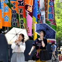Women holding parasols walk along the Ryogoku Kokugikan Sumo arena in Tokyo's Sumida Ward on Sunday morning. | KYODO