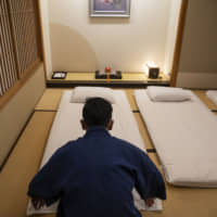 A Kagetsu employee prepares futon for guests at the spa, situated in Niigata Prefecture's Echigo-Yuzawa district. | BLOOMBERG