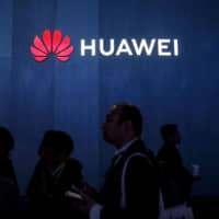 Attendees walk past a sign advertising Huawei Technologies Co. at the 2019 Consumer Electronics Show in Las Vegas in January. | BLOOMBERG