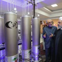 In this photo made available April 9 by the Iranian presidential office, Iranian President Hassan Rouhani listens to the head of Iran's nuclear technology organization, Ali Akbar Salehi, on Nuclear Technology Day in Tehran. | AFP-JIJI