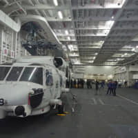 A helicopter sits inside the internal hangar of the Izumo at the Maritime Self-Defense Force base in Yokosuka, Kanagawa Prefecture, in March.