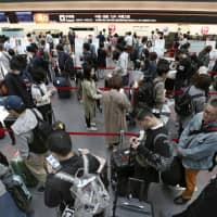 People form a long line Wednesday at a Japan Airlines check-in counter, at Haneda airport in Tokyo, after the airline's automated check-in system suffered a system glitch. | KYODO