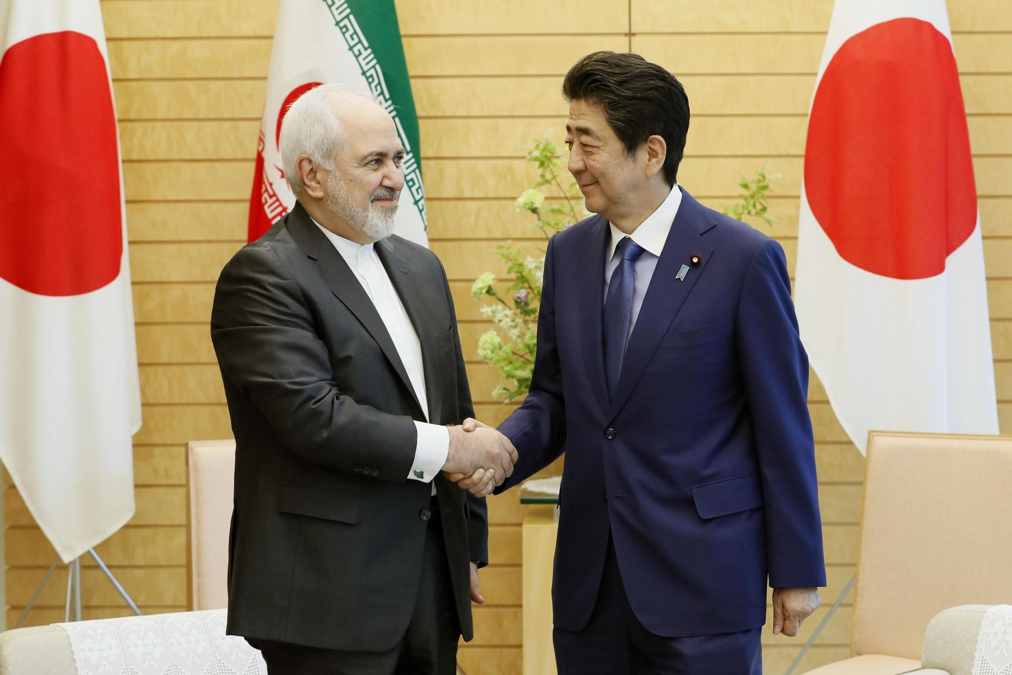 Prime Minister Shinzo Abe and Iranian Foreign Minister Mohammad Javad Zarif shake hands at the Prime Minister's Office on Thursday. | KYODO