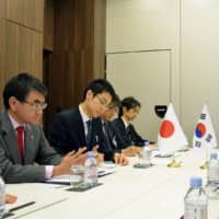 Foreign Minister Taro Kono holds talks with his South Korean counterpart Kang Kyung-wha (right) Thursday in Paris. | POOL / VIA KYODO