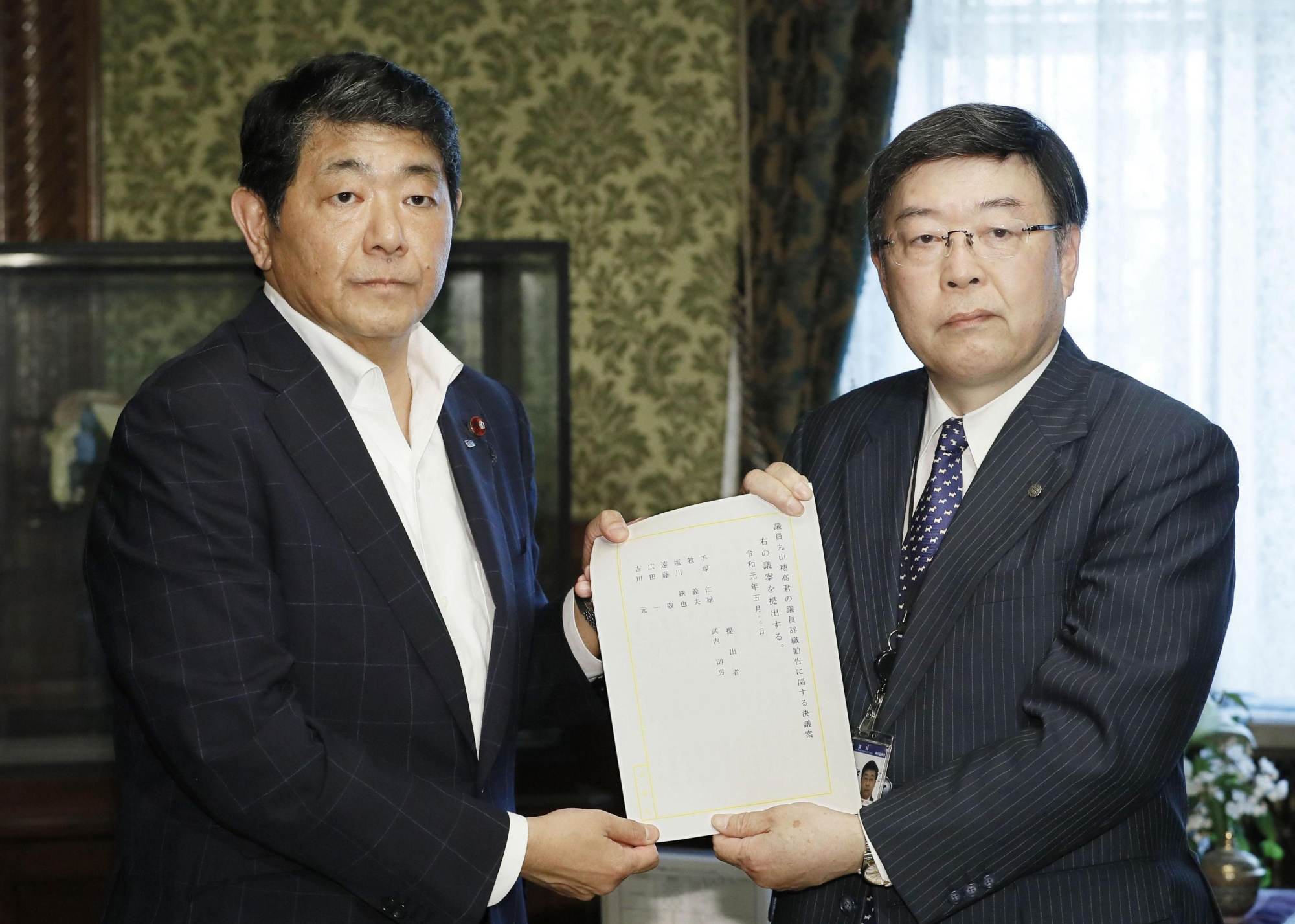 Yoshio Tezuka (left) of the Constitutional Democratic Party of Japan submits a joint motion to the House of Representatives on Friday urging Hodaka Maruyama to resign. | KYODO