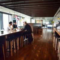 A cafe in real estate company CBRE's Tokyo office doubles as a bar in the evening and offers free drinks during happy hour on days the company designates as no-overtime days. The cafe also serves as a venue for cross-department collaboration. | MASUMI KOIZUMI
