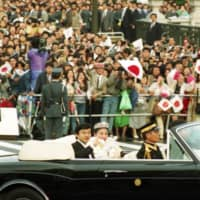 Crown Prince Naruhito and Crown Princess Masako wave during a wedding parade in Tokyo in June 1993. | KYODO