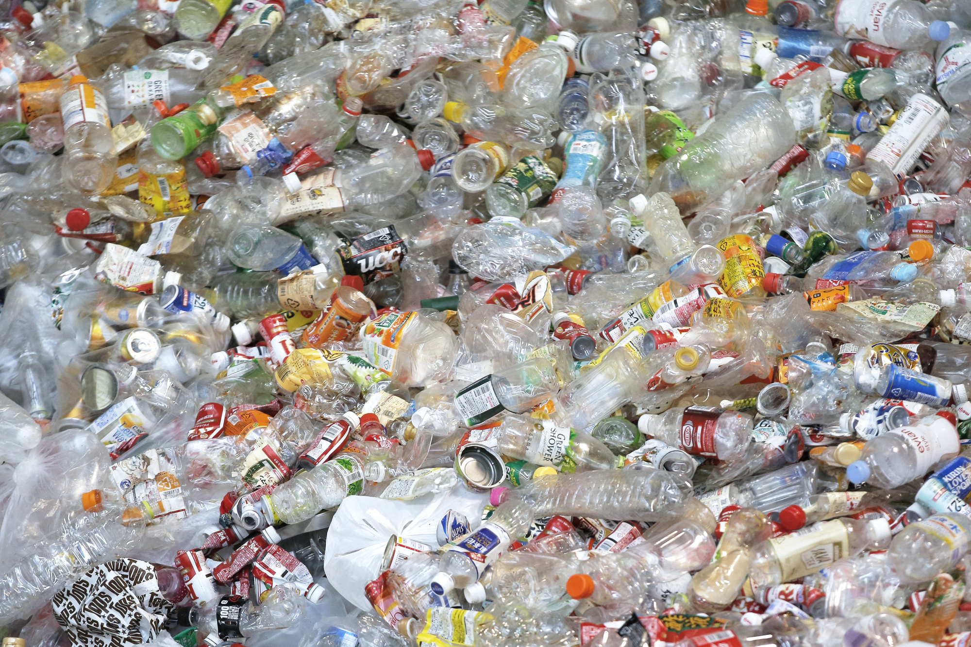 Unsorted plastic bottles pile up at a recycling center in Kawasaki. The government reportedly plans to ask local governments to deal with the growing amount of industrial plastic waste in Japan after China banned imports of such materials. | BLOOMBERG