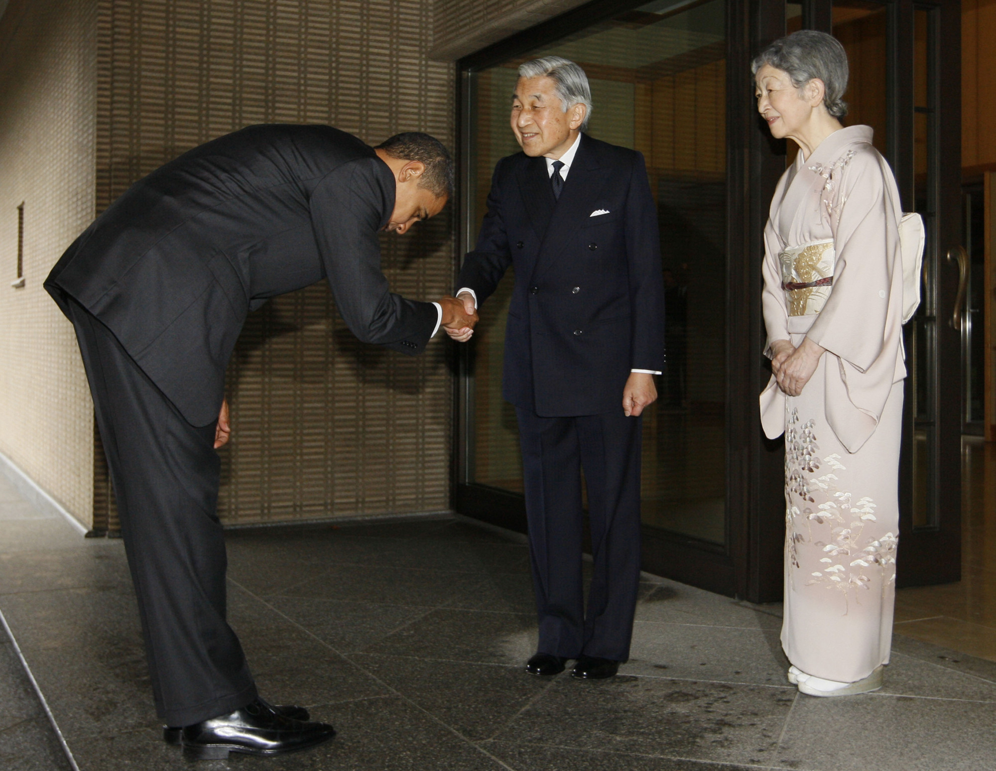 U.S. President Barack Obama bows deeply while shaking hands with Emperor Akihito at the Imperial Palace in Tokyo in November 2009. | AP / VIA KYODO