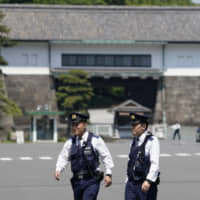 Police officers stand guard outside the Imperial Palace in Tokyo on Friday. U.S. President Donald Trump is scheduled to meet with newly crowned Emperor Naruhito and Prime Minister Shinzo Abe during a four-day visit to Japan that begins Saturday. | BLOOMBERG