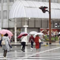 People walk in the rain in the city of  Miyazaki on Saturday. Torrential rain fell on parts of southern Kyushu the same day and, due to a damaged road on Yakushima Island, in Kagoshima Prefecture, about 200 people were still stranded as of Saturday evening.   KYODO