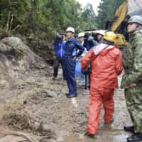 Kagoshima Gov. Satoshi Mitazono (second from left) inspects the location of a mudslide on Yakushima island on Monday, a day after hundreds of stranded hikers were rescued. | KYODO