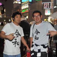 Two men wearing T-shirts printed with the Reiwa kanji character pose for a photo before the dawn of the Reiwa Era at the scramble crossing in front of Tokyo's Shibuya Station on Tuesday. | KAZUAKI NAGATA