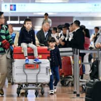 The international arrival floor of Narita airport near Tokyo is packed Sunday as many people return to Japan following an extended Golden Week holiday. | KYODO