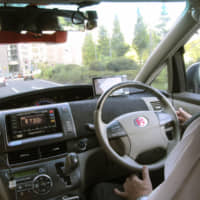 A driver lightly places his hands on the steering wheel during a test run of an autonomous taxi in Tokyo in August. | KYODO