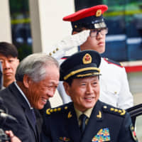 Chinese Defense Minister Wei Fenghe (right) is greeted by his Singaporean counterpart, Ng Eng Hen, during a welcoming ceremony in Singapore on Wednesday. | AFP-JIJI
