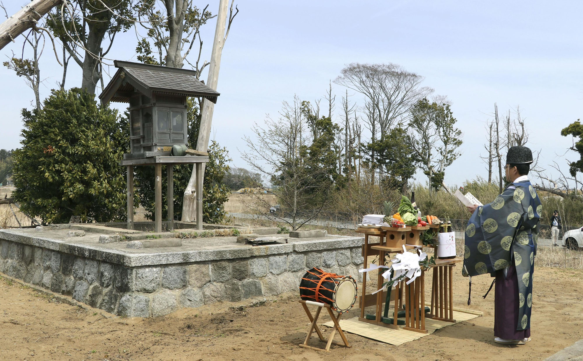 Chief priest Hirohisa Takakura conducts a ritual in front of the temporary pavilion of Hachiman Shrine in the town of Futaba, Fukushima Prefecture, in April. | KYODO