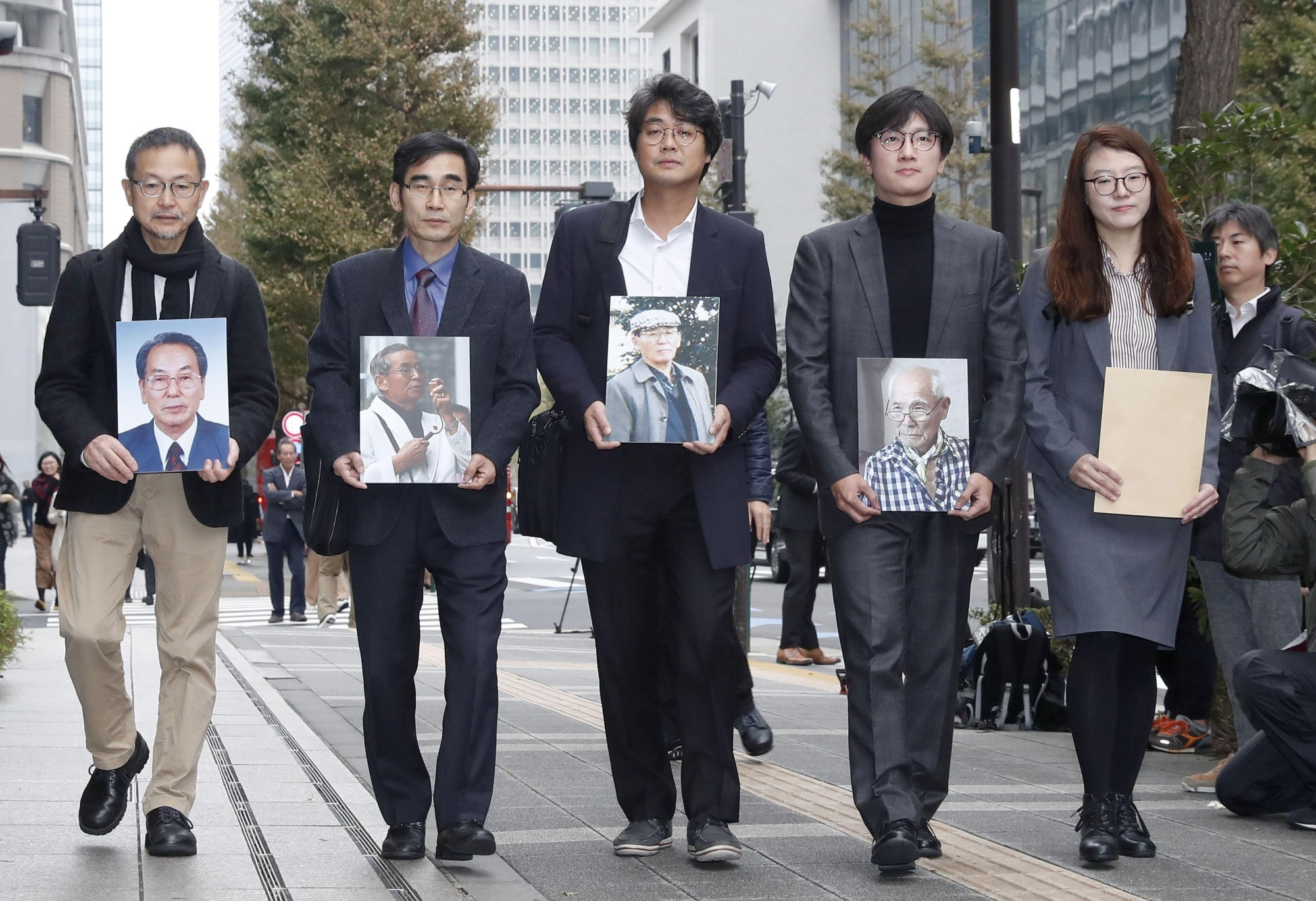 Lawyers representing South Koreans who said they were forced to work for Japan Iron & Steel Co., now known as Nippon Steel Corp., are seen outside the company's head office in Tokyo in November.   KYODO