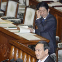 Chief Cabinet Secretary Yoshihide Suga addresses the Lower House plenary session as Prime Minister Shinzo Abe looks on in October 2013. | KYODO