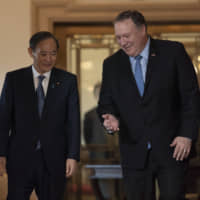 Chief Cabinet Secretary Yoshihide Suga speaks with U.S. Secretary of State Mike Pompeo on Thursday at the State Department in Washington. | AP