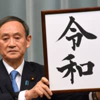Chief Cabinet Secretary Yoshihide Suga holds up a placard showing the kanji for Reiwa, the name of the new Imperial era, at a news conference at the Prime Minister's Office in Tokyo on April 1. | SATOKO KAWASAKI