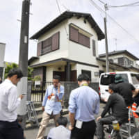 Reporters gather Wednesday in front of the Kawasaki home of Ryuichi Iwasaki, the man behind the mass stabbing a day earlier, as police officials raid the house. | KYODO