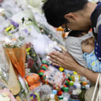 A man offers a prayer Wednesday for victims and those wounded at the scene of a mass stabbing in Kawasaki that occurred the previous day. | KYODO