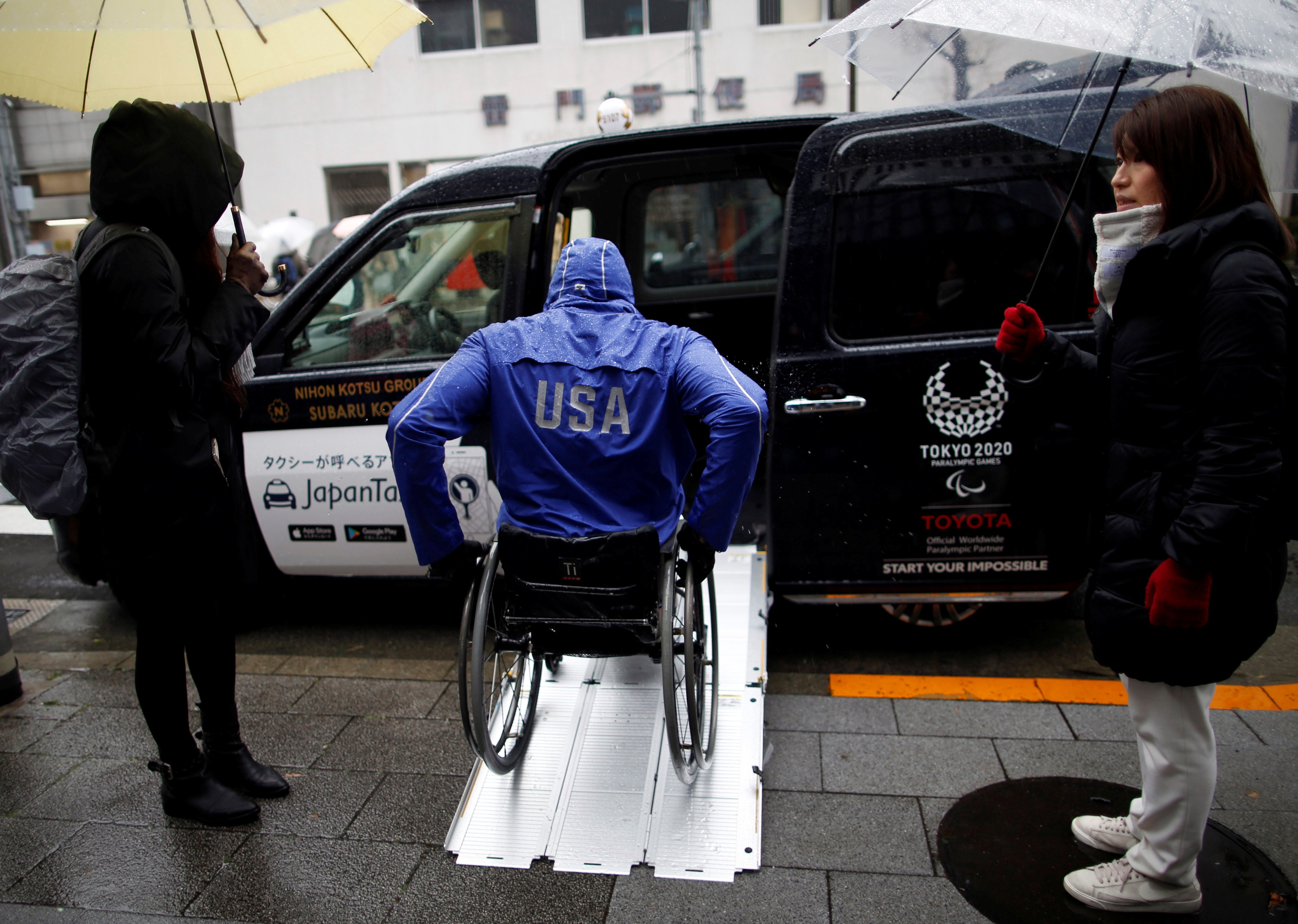 Paralympian Daniel Romanchuk enters a Japan Taxi during his tour of Tokyo on March 4. | REUTERS