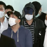 Suspects in a large-scale phone scam in Thailand, involving what is believed to be hundreds of victims across Japan, arrive at Tokyo's Haneda airport on Friday. | KYODO