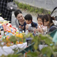 People pay their respects on Thursday to victims of a two-car collision that left two 2-year-old pedestrians dead and several others injured in Otsu, Shiga Prefecture, the previous day. | KYODO