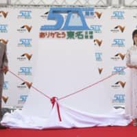 Saori Yoshida (third from right) and others attend a ceremony marking the 50th anniversary of the full opening of Japan's key artery, the Tomei Expressway, in Oyama, Shizuoka Prefecture, on Sunday. | KYODO