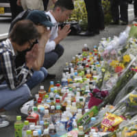 People pray on Wednesday for victims of a mass stabbing attack in Kawasaki a day earlier. | AP