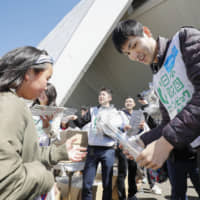 Yoshihiro Muramatsu (right), who lost his sight when he was a junior high school student, hands out commemorative bags to attendees at the main entrance of a long-distance road relay event at Komazawa Olympic Park in Tokyo in March.   KYODO