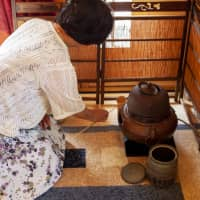 Keeping up traditions: Kumiko Imai-Duxfield prepares a tea ceremony at a teahouse she and her husband, Stephen, built in the backyard of her home and bed and breakfast in Sandspit, New Zealand. | TODD PACEY