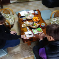 Rina Kambayashi, 53, speaks to Hiroshi Yagi in April about an encounter with a wolf-like animal at her home in Chichibu, Saitama Prefecture, in December last year. | ALEX MARTIN