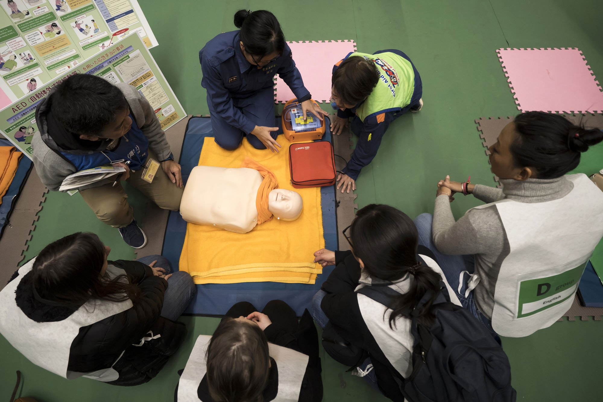Participants learn how to perform cardiopulmonary resuscitation during a disaster preparedness drill for foreign residents in Tokyo on Jan. 16. | BLOOMBERG