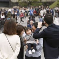 Last Heisei portrait: A family poses for a photo in commemoration of the end of Heisei Era at the Imperial Palace in Tokyo on April 30. Many people spent time away from their computers during the recent 10-day Golden Week. | KYODO