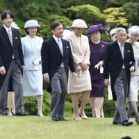 Members of the imperial family walk together at an imperial garden party in April 2018. | KYODO