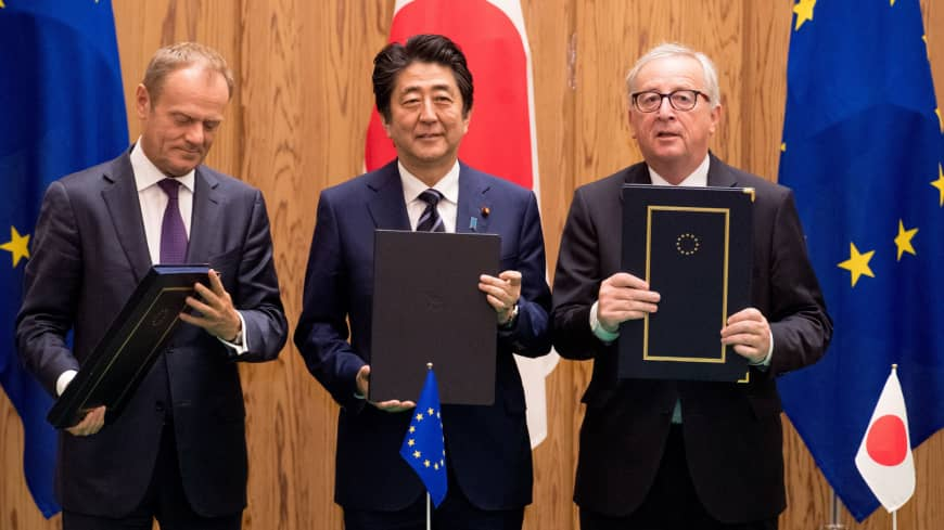 European Council President Donald Tusk, Prime Minister Shinzo Abe and European Commission President Jean-Claude Juncker hold up the signed versions of the economic partnership agreement and the strategic partnership agreement in Tokyo last July.   ETIENNE ANSOTTE, EUROPEAN UNION