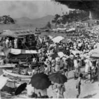 Summertime sojourn: Holidaygoers gather on a beach on Shiraishi Island in August 1955. The island was a popular spot for people looking to get away from the hustle and bustle of mainland cities. | COURTESY OF THE SHIRAISHI ISLAND ARCHIVES