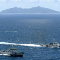 A Japan Coast Guard ship (right) and a Chinese surveillance ship sail in Japanese waters off the northeastern coast of Uotsuri, one of the five main islets in the Senkaku Islands chain, on Sept. 14, 2012. The territorial dispute has been a flash point in Japan-China relations since 2012 when the Japanese government nationalized the uninhabited islets. | KYODO