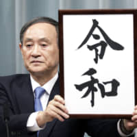 Chief Cabinet Secretary Yoshihide Suga unveils the new imperial era name April 1, earning him the nickname 'Uncle Reiwa' and fueling speculation about his political future. | BLOOMBERG