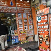 Sticking around: A man walks into an internet cafe in Tokyo's Akihabara district last year. While some internet cafes are still around, they are nowhere near as commonplace as they once were. | SATOKO KAWASAKI