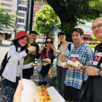 Snack time: The team gathers to refuel during the more than 11-hour Yamathon trek that took place on May 11. The walking course follows Tokyo's central Yamanote railway line. | AYA ITO