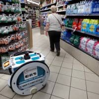 A woman in Paris does her shopping at a store using an autonomous robot. | REUTERS