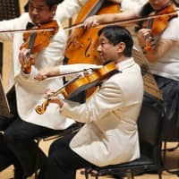 Crown Prince Naruhito plays the viola during a concert of Gakushuin University alumni in Tokyo on July 7, 2013. | AP