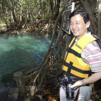 Crown Prince Naruhito views a cenote (sinkhole) in Celestun, Mexico, on March 19, 2006. | AP
