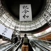 A huge banner and screen celebrating Reiwa, Japan's new imperial era, are displayed Wednesday on the first day of Emperor Naruhito's accession to the throne in a Tokyo business district. | REUTERS